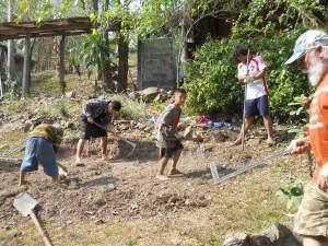 Bamboo School boys level the hillside for the aqua-ponics system.
