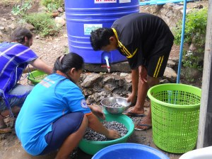 Conagee and Matthew wash gravel for the Aqua-ponics grow beds.